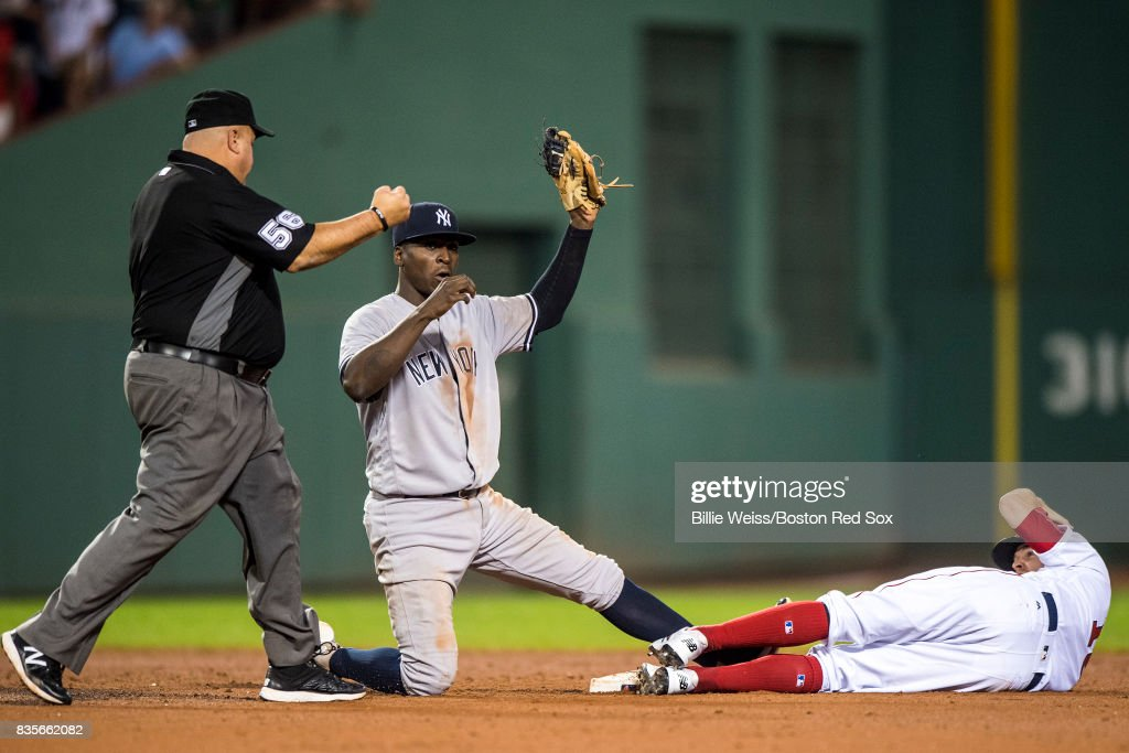 Brock Holt #12 of the Boston Red Sox is tagged out by Didi Gregorius #18 of the New York Yankees while attempting to steal during the ninth inning of a game on August 19, 2017 at Fenway Park in Boston, Massachusetts.