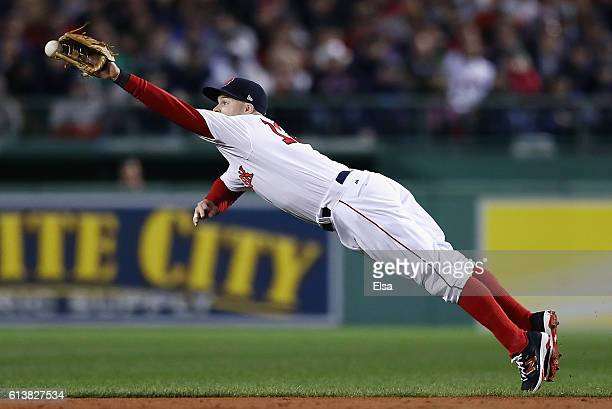 Brock Holt of the Boston Red Sox is unable to catch a ball hit by Lonnie Chisenhall of the Cleveland Indians in the second inning during game three...