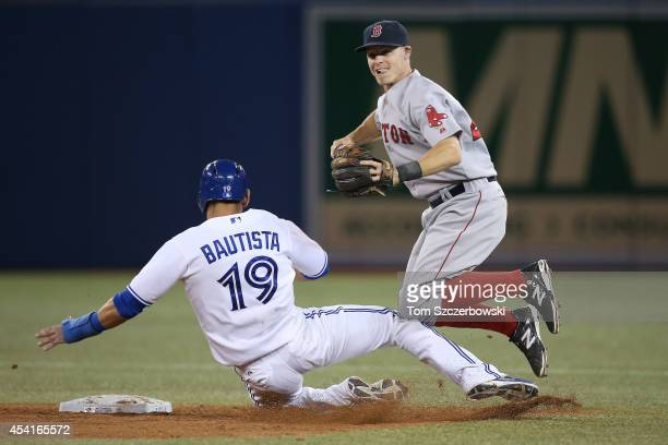 Brock Holt of the Boston Red Sox is upended in the ninth inning during MLB game action by Jose Bautista of the Toronto Blue Jays who breaks up a...