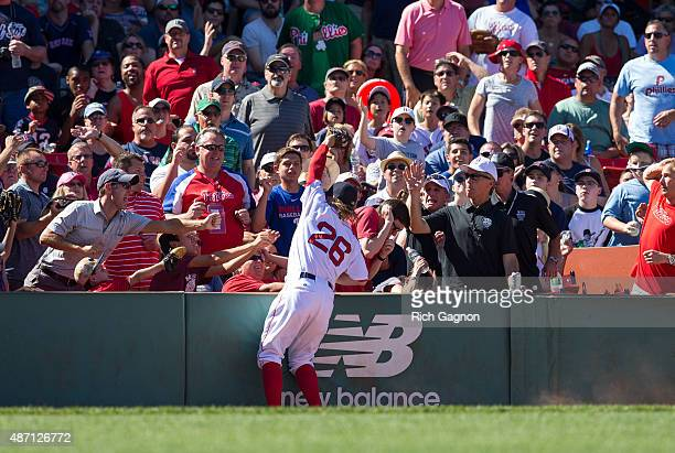 Brock Holt of the Boston Red Sox makes a catch on a ball hit by Jeff Francoeur of the Philadelphia Phillies while leaning into the stands during the...