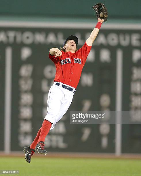Brock Holt of the Boston Red Sox makes a leaping catch on a ball hit by Nelson Cruz of the Seattle Mariners in the eighth inning at Fenway Park on...