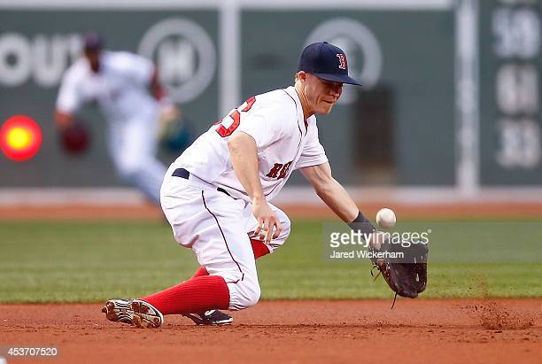 Brock Holt of the Boston Red Sox misplays a ground ball at third base in the first inning against the Houston Astros during the game at Fenway Park...