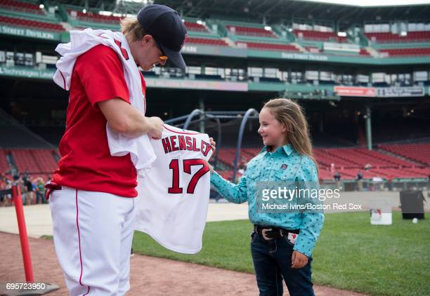 Brock Holt of the Boston Red Sox presents a jersey to Macey Hensley, a frequent guest on the Ellen DeGeneres show, at Fenway Park on June 13, 2017 in...