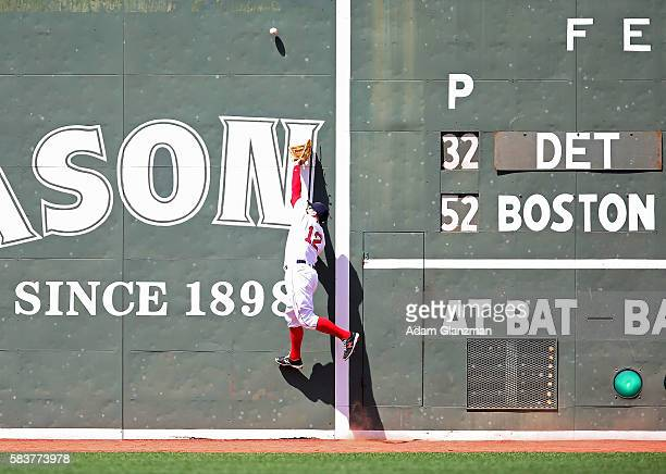 Brock Holt of the Boston Red Sox reaches for a ball that bounces of the Green Monster in the third inning during the game against the Detroit Tigers...