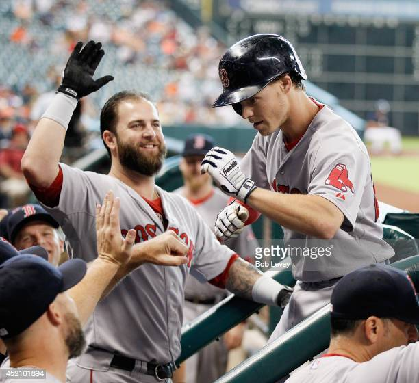 Brock Holt of the Boston Red Sox revceives high fives from Mike Napoli after hitting a home run in the first inning against the Houston Astros at...