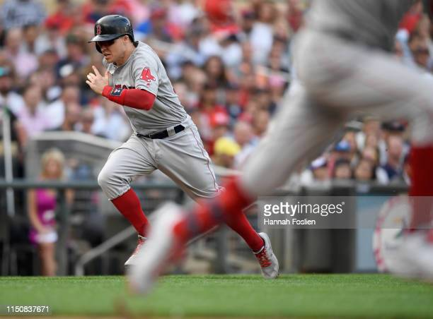 Brock Holt of the Boston Red Sox runs towards home plate to score a run on an infield single from teammate Mookie Betts against the Minnesota Twins...