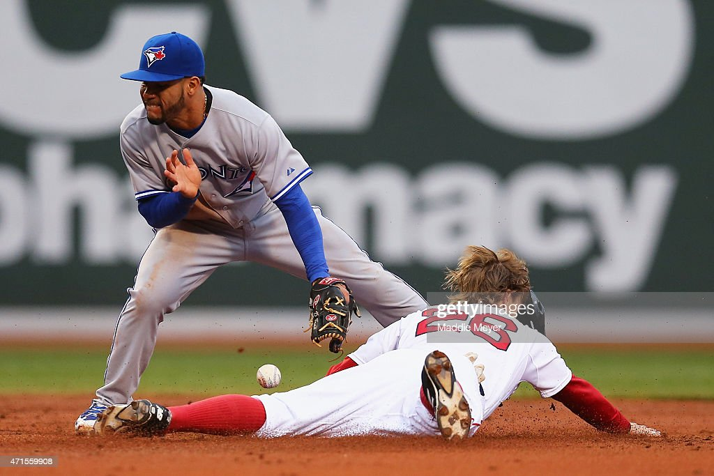 Brock Holt #26 of the Boston Red Sox safely steals second, evading a tag from Devon Travis #29 of the Toronto Blue Jays during the second inning at Fenway Park on April 29, 2015 in Boston, Massachusetts.
