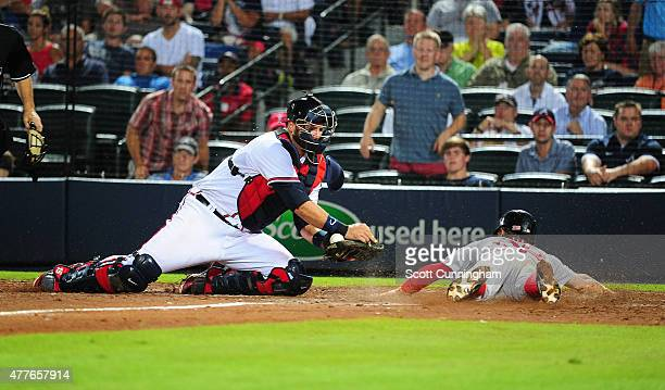 Brock Holt of the Boston Red Sox scores a seventh inning run against A J Pierzynski of the Atlanta Braves at Turner Field on June 18 2015 in Atlanta...