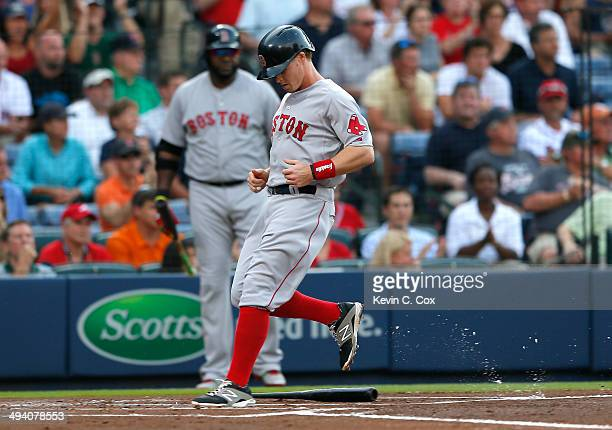 Brock Holt of the Boston Red Sox scores on a sacrifice fly by Dustin Pedroia in the first inning against the Atlanta Braves at Turner Field on May 27...
