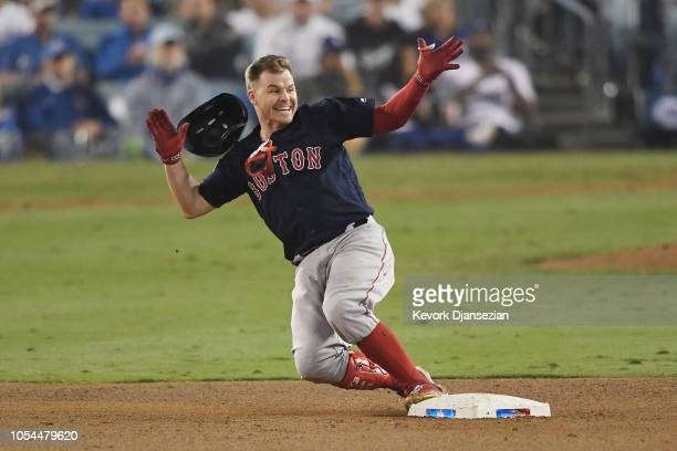 Brock Holt of the Boston Red Sox slides into second base on his oneout double to left field in the ninth inning of Game Four of the 2018 World Series...