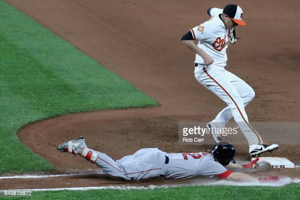 Brock Holt of the Boston Red Sox slides into the bag ahead of the tag by pitcher Brad Brach of the Baltimore Orioles for an infield hit in the...