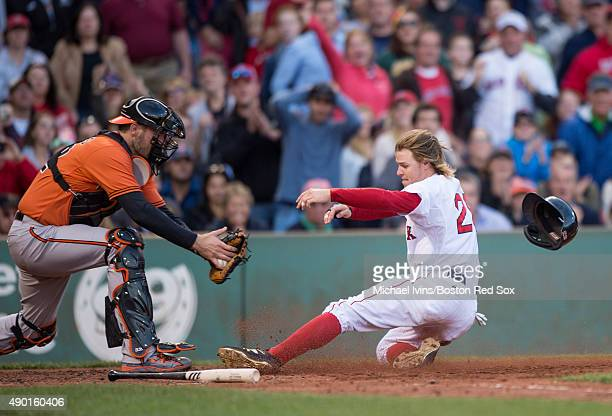 Brock Holt of the Boston Red Sox slides under the tag of Matt Wieters of the Baltimore Orioles to score a run during the fifth inning at Fenway Park...