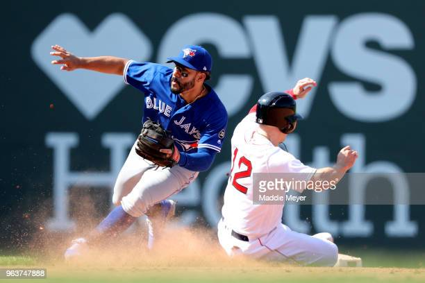 Brock Holt of the Boston Red Sox steals second past Devon Travis of the Toronto Blue Jays during the eighth inning at Fenway Park on May 30 2018 in...