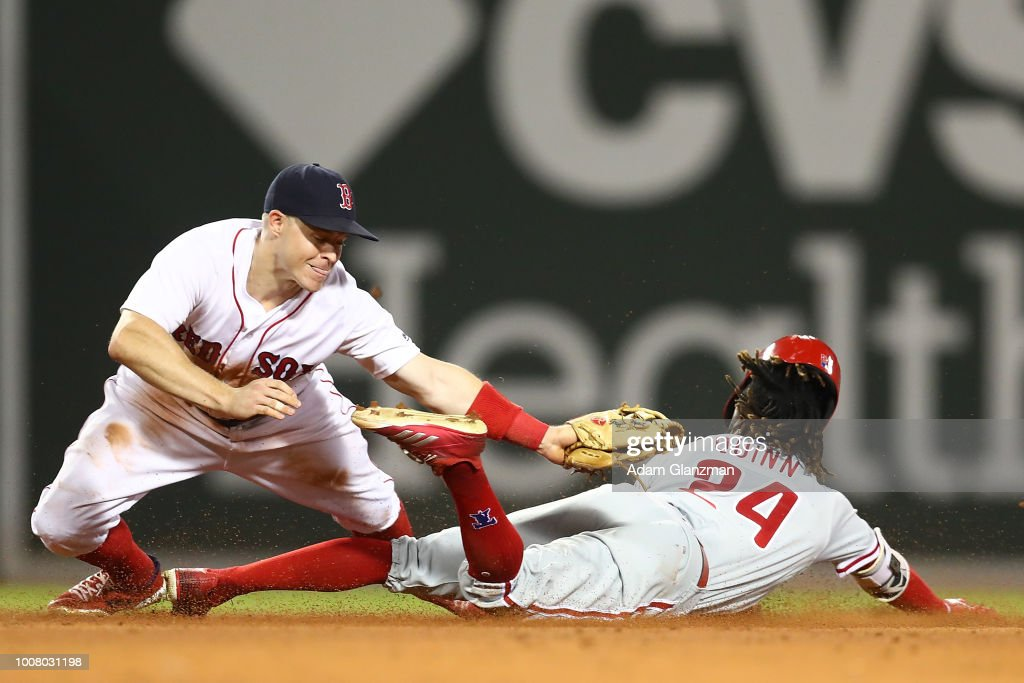 Brock Holt #12 of the Boston Red Sox tags out Roman Quinn #24 of the Philadelphia Phillies as he attempts to steal second base in the ninth inning of a game at Fenway Park on July 30, 2018 in Boston, Massachusetts.