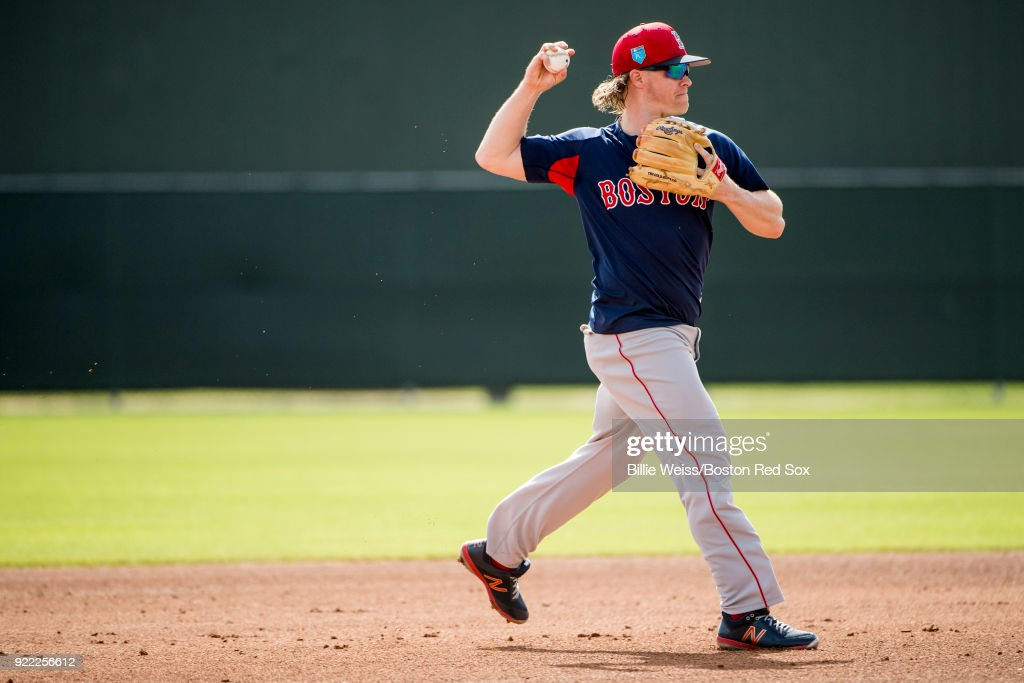 Brock Holt #12 of the Boston Red Sox throws during a team workout on February 21, 2018 at jetBlue Park at Fenway South in Fort Myers, Florida .