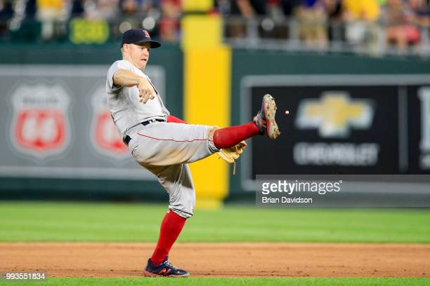 Brock Holt of the Boston Red Sox tries to kick a piece of a gum after the Boston Red Sox defeated the Kansas City Royals at Kauffman Stadium on July...