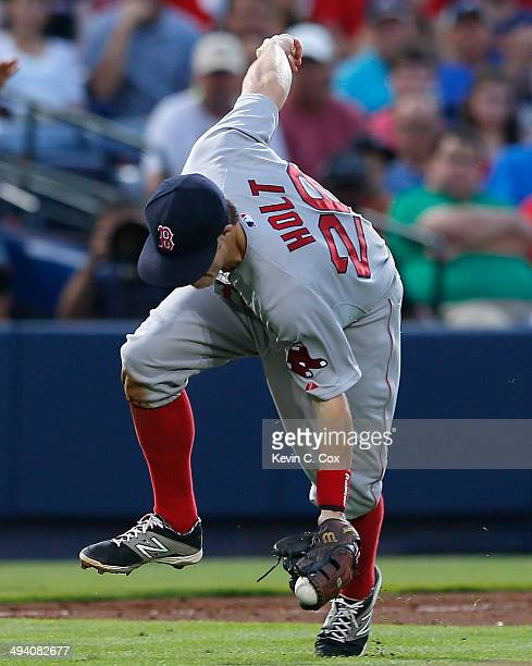 Brock Holt of the Boston Red Sox tries to make a play as he scoops up a ground ball by Andrelton Simmons of the Atlanta Braves in the third inning at...