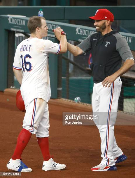 """Brock Holt of the Texas Rangers and manager Chris Woodward celebrate Holt""""u2019s eleventh inning walk-off single against the San Francisco Giants at..."""