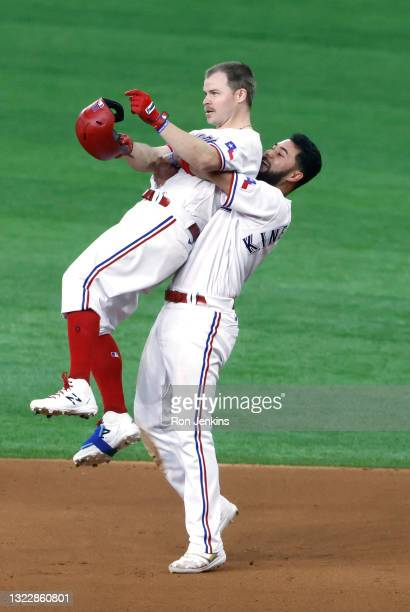 """Brock Holt of the Texas Rangers and teammate Isiah Kiner-Falefa celebrate Holt""""u2019s eleventh inning walk-off single against the San Francisco..."""