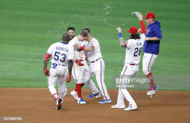 Brock Holt of the Texas Rangers and teammates celebrate Holt's eleventh inning walk-off single against the San Francisco Giants at Globe Life Field...