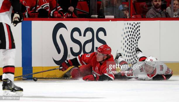 Brock McGinn of the Carolina Hurricanes and Matt Duchene of the Ottawa Senators collide and go down on the ice as they battle for the loose puck...