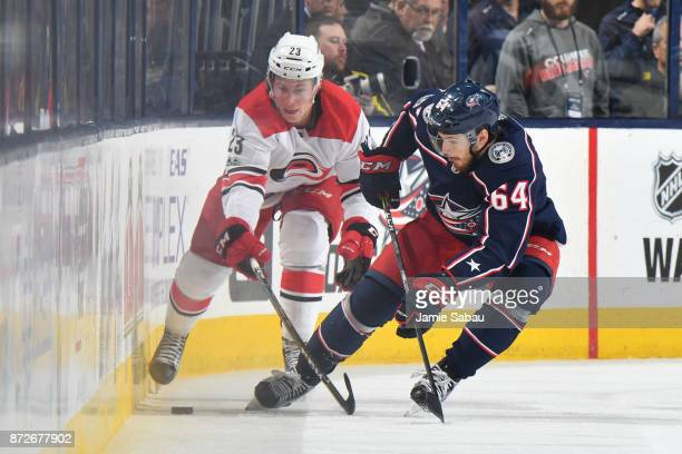 Brock McGinn of the Carolina Hurricanes and Tyler Motte of the Columbus Blue Jackets battle for a loose puck against the board during the second...