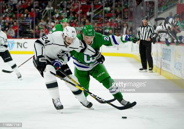 Brock McGinn of the Carolina Hurricanes battles for a loose puck with Derek Forbort of the Los Angeles Kings during an NHL game on January 11 2020 at...