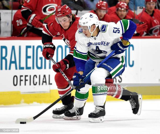 Brock McGinn of the Carolina Hurricanes battles Troy Stecher of the Vancouver Canucks for the puck during the first period of their game at PNC Arena...