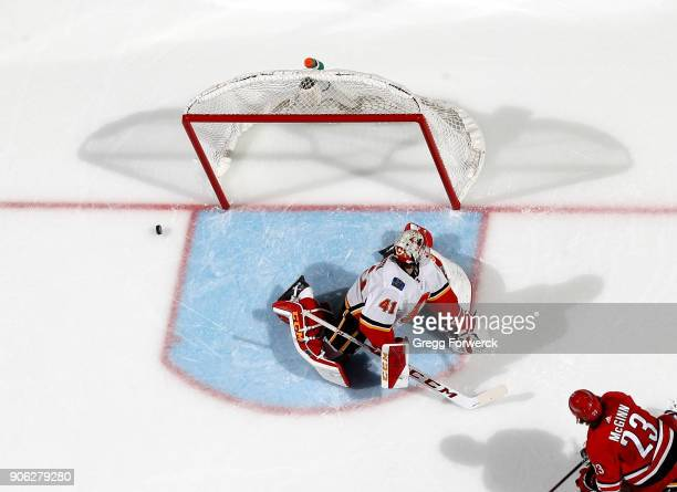 Brock McGinn of the Carolina Hurricanes shoots a puck that rings off both pipes as Mike Smith of the Calgary Flames attempts to make a save during an...