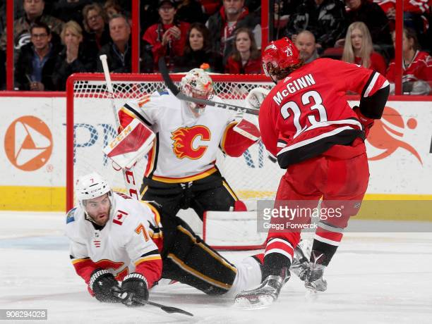 Brock McGinn of the Carolina Hurricanes shoots a puck that rings off both pipes as Mike Smith of the Calgary Flames attempts to make a save and...