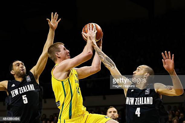 Brock Motum of the Boomers attempts to shoot past the defence of Everard Bartlett and Lindsay Tait of the Tall Blacks during the game two match...
