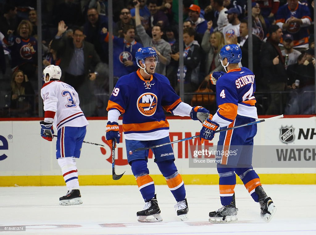 Brock Nelson #29 and Dennis Seidenberg #4 of the New York Islanders celebrate Seidenberg's third period goal against the Montreal Canadiens at the Barclays Center on October 26, 2016 in the Brooklyn borough of New York City. The Canadiens defeated the Islanders 3-2.