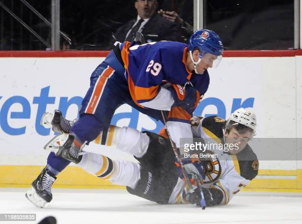 Brock Nelson of the New York Islanders and Charlie McAvoy of the Boston Bruins bounce off the boards into a heap during the second period at the...