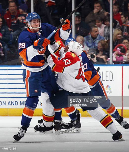Brock Nelson of the New York Islanders battles with Mike Weaver of the Florida Panthers during the second period at the Nassau Veterans Memorial...