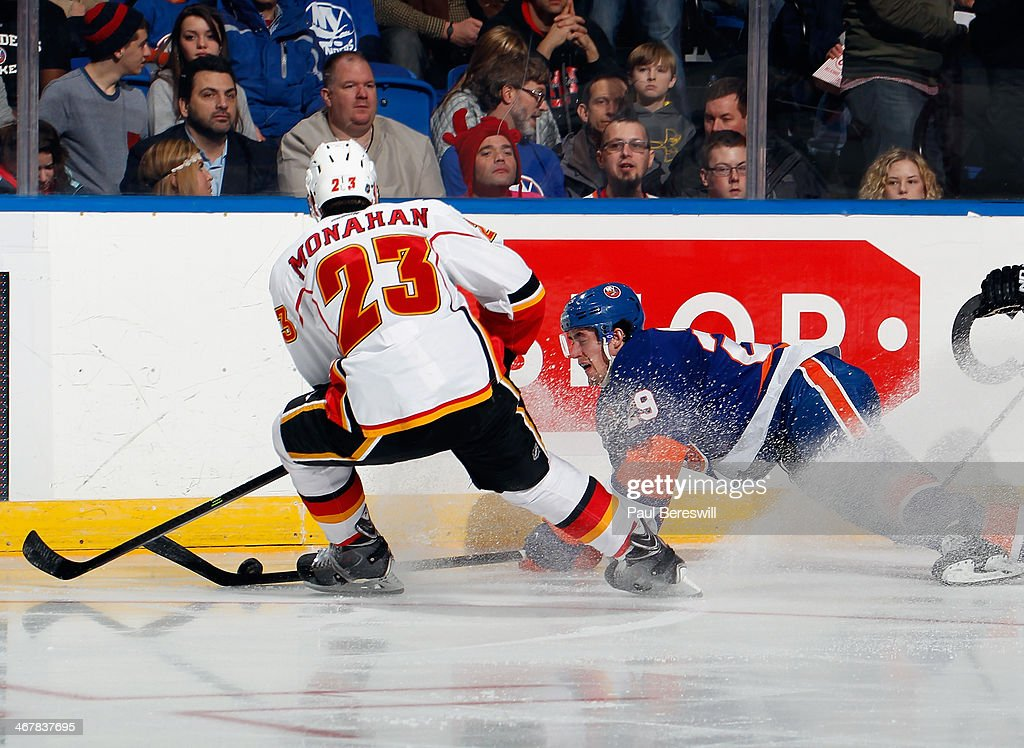 Brock Nelson #29 of the New York Islanders falls to the ice in front of Sean Monahan #23 of the Calgary Flames during an NHL hockey game at Nassau Veterans Memorial Coliseum on February 6, 2014 in Uniondale, New York.