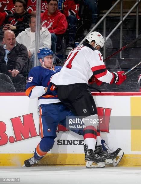 Brock Nelson of the New York Islanders is checked into the boards by Brian Boyle of the New Jersey Devils during the game at Prudential Center on...