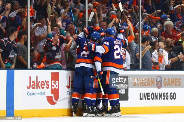 Brock Nelson of the New York Islanders is congratulated by his teammates after scoring a goal against the Boston Bruins during the second period in...