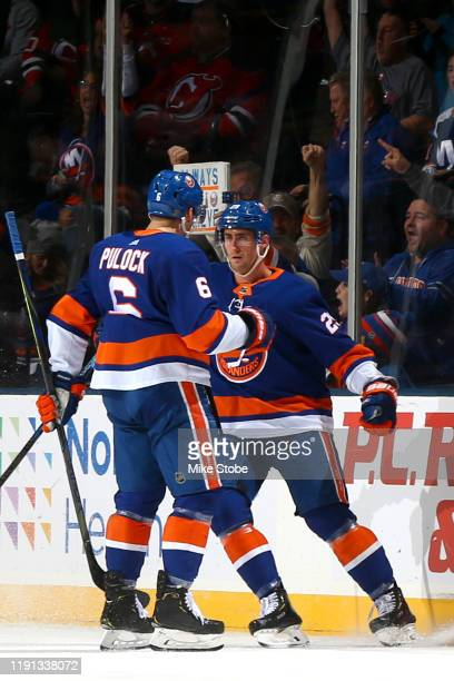 Brock Nelson of the New York Islanders is congratulated by his teammate Ryan Pulock after scoring a goal against the New Jersey Devils during the...