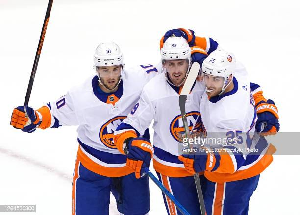 Brock Nelson of the New York Islanders is congratulated by teammates Derick Brassard and Devon Toews after Nelson scored in the second period against...