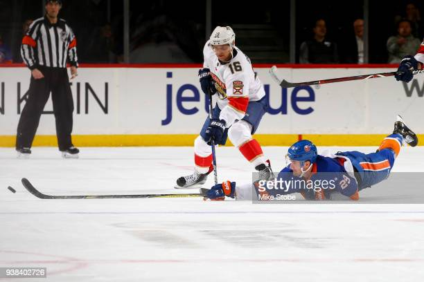 Brock Nelson of the New York Islanders makes a sliding pokecheck to knock the puck away from Aleksander Barkov of the Florida Panthers during the...