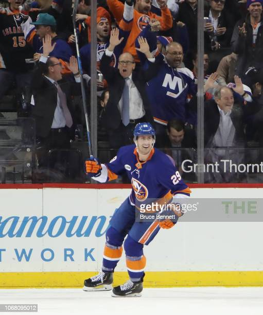 Brock Nelson of the New York Islanders scores a first period goal against the New York Rangers as team owner Jon Ledecky celebrates behind him at the...
