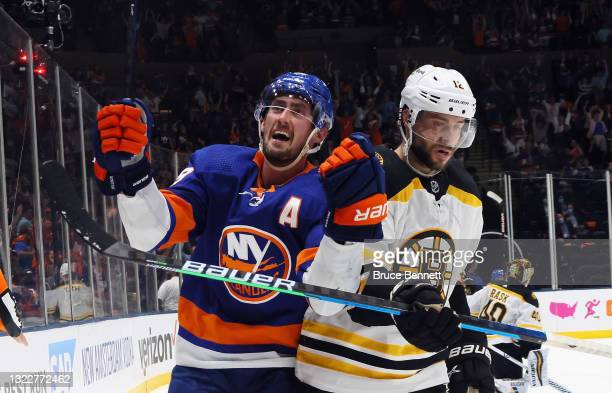 Brock Nelson of the New York Islanders scores at 12:39 of the second period against the Boston Bruins as Craig Smith moves away in Game Six of the...