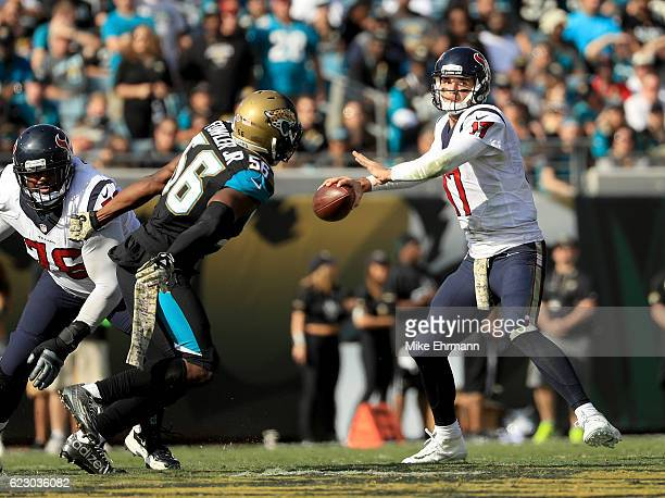 Brock Osweiler of the Houston Texans attempts a pass as Dante Fowler of the Jacksonville Jaguars closes in during the game at EverBank Field on...
