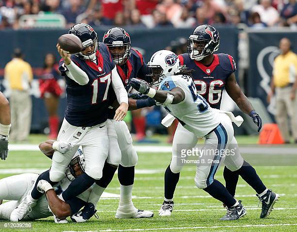 Brock Osweiler of the Houston Texans is pressured by Sean Spence of the Tennessee Titans as he attempts to throw the ball in the second quarter of...