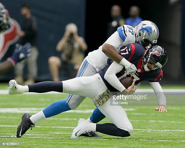 Brock Osweiler of the Houston Texans is sacked by Armonty Bryant of the Detroit Lions at NRG Stadium on October 30 2016 in Houston Texas