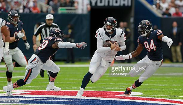 Brock Osweiler of the Houston Texans scrambles out of the pocket to avoid Leonard Floyd of the Chicago Bears and Danny Trevathan at NRG Stadium on...