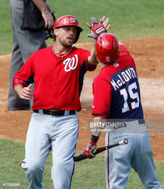 Brock Peterson is congratulated by Nate McLouth of the Washington Nationals after scoring against the St Louis Cardinals in the third inning during a...