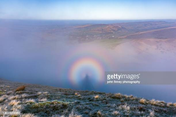 brocken spectre above the village of hayfield, derbyshire, peak district. uk - atmospheric mood stock pictures, royalty-free photos & images