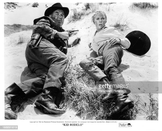 Broderick Crawford crouches next to Janet Leigh in a scene from the film 'Kid Rodelo' 1966