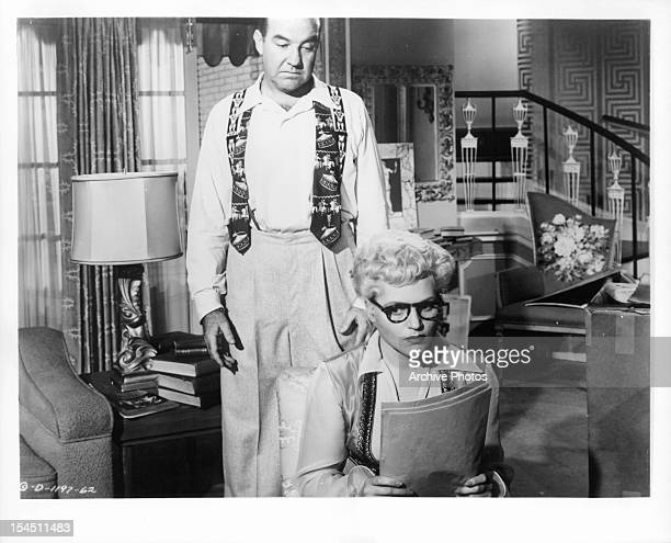 Broderick Crawford looks over the shoulder of Judy Holliday in a scene from the film 'Born Yesterday' 1950